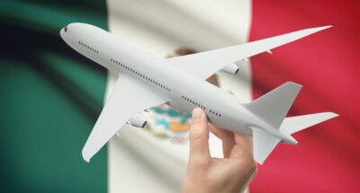 Airplane,In,Hand,With,National,Flag,On,Background,-,Mexico